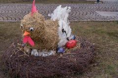 Gallina della paglia con le uova variopinte Fotografia Stock
