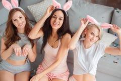 Gallina-partido Mujeres jovenes en los oídos del conejito en casa junto que se sientan cerca del sofá que presenta a la opinión s
