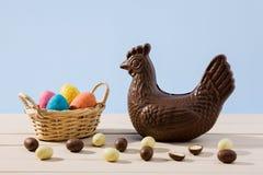 Gallina y huevos del chocolate de Pascua en una tabla Fotos de archivo libres de regalías