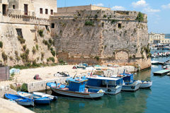 Gallipoli, Angevin castle with fishing boats. Back side of the Angevin castle in Gallipoli, Salento region (Apulia) with the tower and some fishing boats in the stock photography