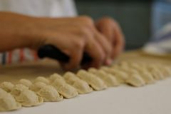 Close up of pasta making process. Woman makes orecchiette, ear shaped pasta, traditional to the Puglia region of Italy. Gallipoli, Italy. Close up of pasta stock image