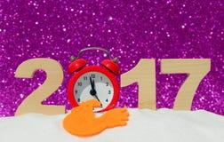 Gallo, despertador y los números 2017 en una nieve acumulada por la ventisca en un backgr rosado del brillo Foto de archivo