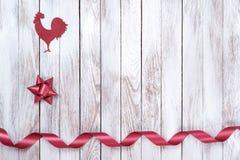 Gallo, estrella, cinta en fondo de madera Concepto de las vacaciones de invierno Año Nuevo del gallo Fotos de archivo