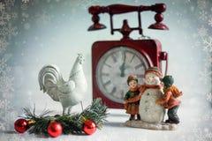 Gallo, niños con un muñeco de nieve en el fondo del reloj Imagenes de archivo