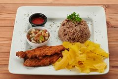 Gallo pinto with salsa and fried meat. In plate on wooden table stock images