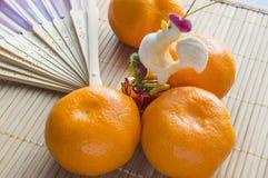 Gallo - símbolo del Año Nuevo chino con las mandarinas y la fan Fotos de archivo libres de regalías