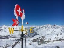Gallo segnavento della banderuola davanti alla valle nella regione dello sci di Zermatt, Svizzera della materia fotografia stock