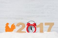 Gallo y los números 2017 en una nieve acumulada por la ventisca en un fondo de madera Imagen de archivo libre de regalías