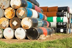 55 Gallon Drums Stacked on Each Other in a Storage Facility. 55 gallon drums layered in stacks on top of each other in a storage yard for waste related drums Stock Photos