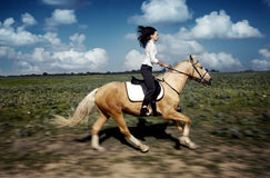 Gallop. Motion blur photo of the woman and horse moving at the gallop Stock Image