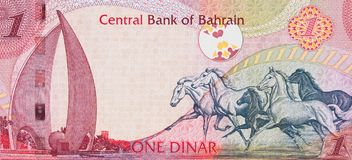 Galloping Arabian Horses and the Sail and Pearl monument on Bahr. Ain one dinar 2006 banknote closeup macro, Bahraini money close up Stock Photos