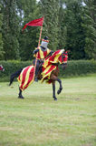 Galloping horse and red flag knight Royalty Free Stock Photography