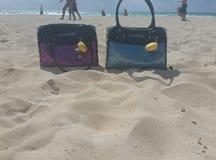 Galna handväskor på stranden Royaltyfri Foto