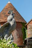 Galo novo de pedra contra uma casa de Kent Oast imagem de stock royalty free
