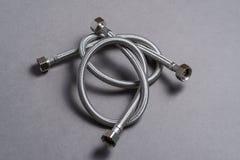 Galonowy stali nierdzewnej wody wąż elastyczny nad popielatym tłem Fotografia Stock