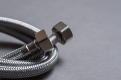 Galonowy stali nierdzewnej wody wąż elastyczny nad popielatym tłem Obraz Royalty Free