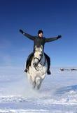 Galope de la equitación de la mujer joven en la nieve Foto de archivo libre de regalías