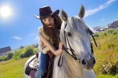 Galope joven del cowgirl en el caballo blanco Foto de archivo libre de regalías