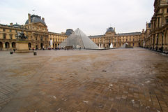 The galss pyramid of the Louvre, Paris. The glass pyramid and the Louvre in a cloudy day in Paris, France Stock Image