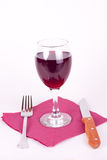 Galss of wine. Glass of wine on napkin with knife and fork Royalty Free Stock Photos