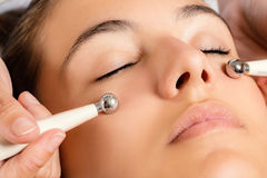 Galvanic facial treatment with low level current electrodes. stock photography