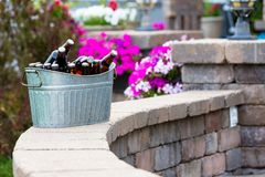 Galvanised metal tub filled with bottles of beer. Galvanised metal tub filled with bottles of craft beer or larger chilling on a curved brick patio wall outdoors stock photo