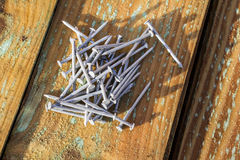 Galvanised Nails. Pile of galvanised nails on planks of wood stock images