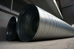 Galvanised steel ducting tubing for air extraction. On the floor of a factory warehouse royalty free stock image