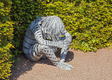 Despair, Galvanised Steel Sculpture, Hampton Court, Herefordshire, England. A galvanised steel sculpture of a sad looking person in the walled garden at Hampton royalty free stock images