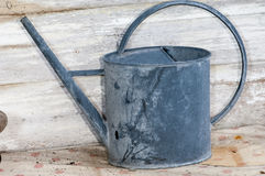 Galvanised watering can. Traditional galvanised watering can on a small table royalty free stock image