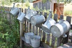 Galvanisierte Gießkannen, die am alten Zaun hängen lizenzfreie stockfotos