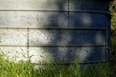 Galvanized bin side with shadows showing in the green grass Royalty Free Stock Photos