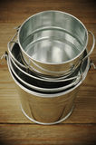 Galvanized buckets. Stack of empty galvanized buckets on rustic wooden background. Toned image Stock Images