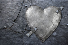 Galvanized metal heart. Photo of a galvanized metal heart bolted to old hammered metal plates with rivets stock images