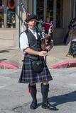Galveston TX/USA - 12 06 2014: Den manliga musikern i traditionell skotsk dräkt spelar harpan på tusan på trådfestivalen i Galv Arkivbilder