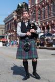 Galveston TX/USA - 12 06 2014: Den manliga musikern i traditionell skotsk dräkt spelar harpan på tusan på trådfestivalen i Galv Fotografering för Bildbyråer