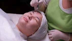 Galwaniczny cleaning skóra Azjatycka kobieta na procedurze disincrustation Praca beautician z elektrycznym appara zdjęcie wideo