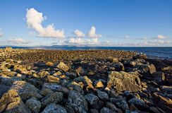 Galway Bay. With a large rock jetty in the foreground. The Burren can be seen in the background with cumulus clouds against a blue sky Stock Photography
