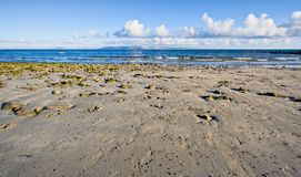 Galway Bay. In Ireland. The photo is layered with sand, water, The Burren (hills), and sky Royalty Free Stock Images