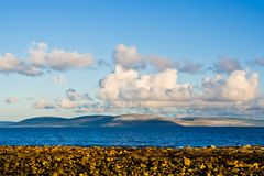 Galway Bay and Burren. Galway Bay in Ireland from the town of Spiddal with The Burren across the bay. Photo is layered from front to back with Rocks, Galway Bay Royalty Free Stock Photo
