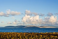 Galway Bay and Burren. Galway Bay in Ireland from the town of Spiddal with The Burren across the bay. Photo is layered from front to back with Rocks, Galway Bay Stock Photos