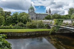 Galway Cathedral and Salmon Weir Bridge, Ireland. Galway, Ireland - August 5, 2017: The Cathedral building with dome and Salmon Weir Bridge leading to it. Under Stock Photo