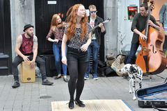Galway, Ireland June 2017,Ginger Hair Girl step dancing in the s. Treet with a group of Irish musicians Royalty Free Stock Photography