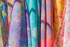 Gama de bufandas de seda coloridas en la tienda fotos de archivo libres de regalías