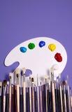 Gama de colores de la pintura del artista con las pinturas y los cepillos, simbólicos de arte Fotos de archivo
