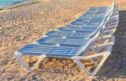 Gama de sillones rayados azules y blancos en una playa arenosa con el océano azul en el fondo Fotografía de archivo libre de regalías