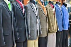 Gama de trajes en maniquíes de la tienda imagen de archivo