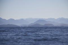 Gama montañosa de la isla en oscuridad azul Foto de archivo