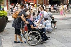 Gamal man i en rullstol på qianmengatan i Peking Arkivbild