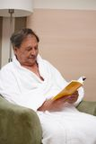 Gamal man i fåtölj som läser en bok Arkivbilder